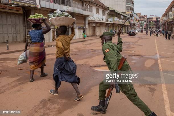 Police officer beats a female orange vendor on a street in Kampala, Uganda, on March 26 after Ugandan President Yoweri Museveni directed the public...