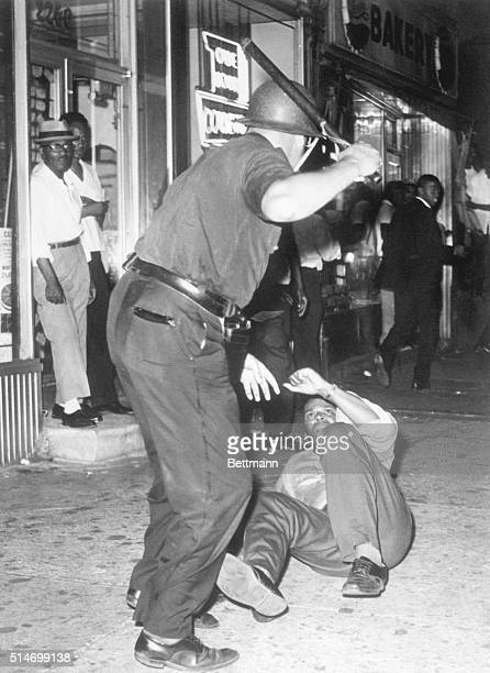 A police officer beats a protester with a nightstick during riots in Harlem sparked by the killing of a 15 year old boy by police