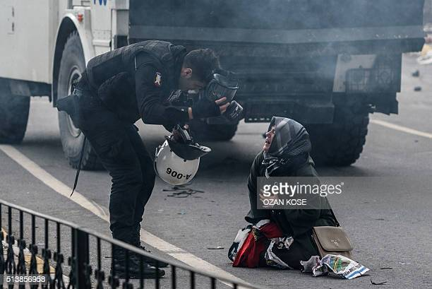 A police officer bends down near a woman crying in the street as Turkish antiriot police officers use tear gas to disperse supporters in front of the...