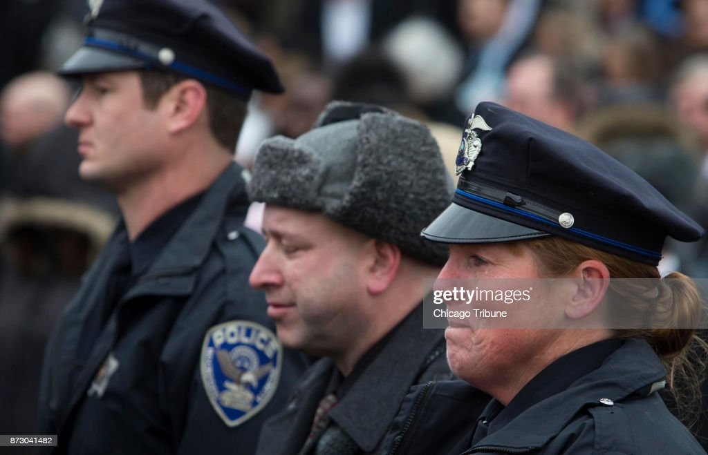 a police officer breaks into tears during the funeral for slain