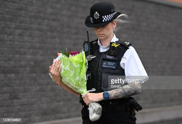 Police officer brings a floral tribute to the Croydon Custody Centre in south London on September 25 following the shooting of a British police...
