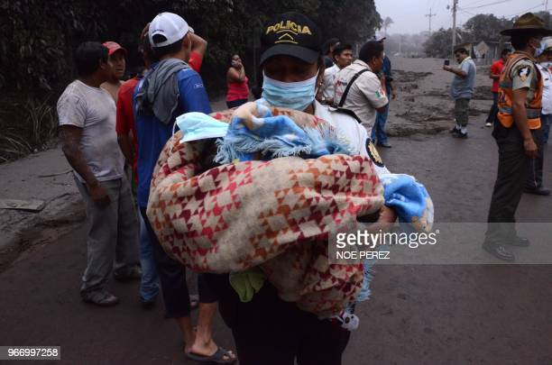 TOPSHOT A police officer carries a baby after the eruption of the Fuego Volcano in El Rodeo village Escuintla department 35 km south of Guatemala...