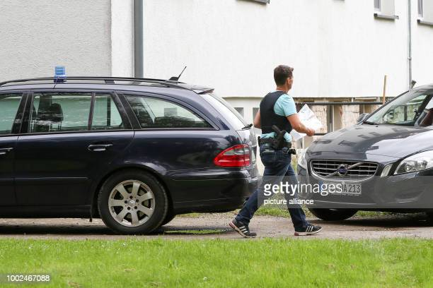 A police officer carries a plastic bag next to an apartment building in Boldebuck Germany 26 July 2017 The police searched several properties in...