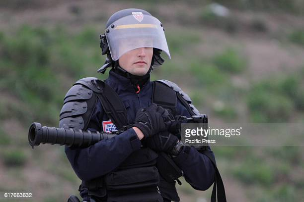 A police officer carries a tear gas granite launcher in his arms while watching the refugees in the Jungle A few dozen refugees and riot police...