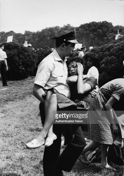 A police officer carries an injured young woman to safety during the March on Washington for Jobs and Freedom Washington DC August 28 1963