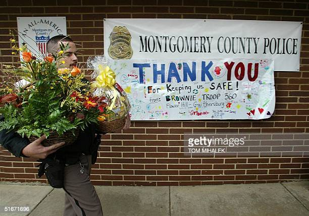 A police officer carries flowers and a fruit basket from wellwishers into the Montgomery County Police headquarters 25 October 2002 in Rockville...