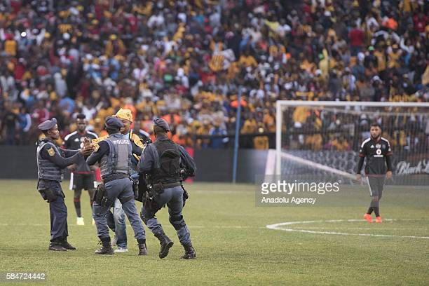Police officer cathces a fan of Kaiser Chiefs during 2016 Carling Black Label Cup between Kaizer Chiefs FC and Orlando Pirates at FNB Stadium in...
