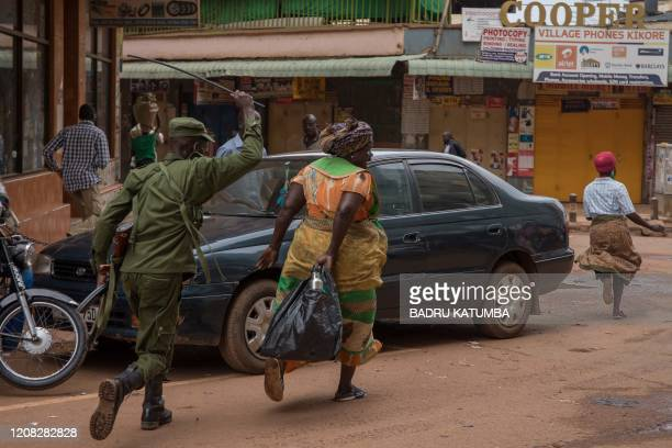 Police officer chases away a woman on a street in Kampala, Uganda, on March 26 after Ugandan President Yoweri Museveni directed the public to stay...