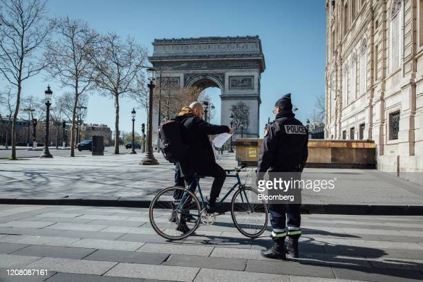 A police officer checks a cyclist's paperwork near the Arc de Triomphe monument during citizen movement restrictions and coronavirus containment...