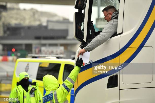 Police officer checks a driver's Covid-19 test documentation at the entrance to the Port of Dover, southeast England, on January 4, 2021 following...