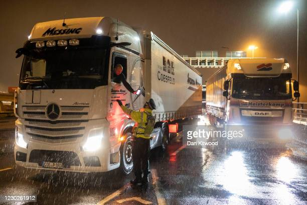 Police officer checks a lorry driver's information as it rains on December 22, 2020 in Dover, United Kingdom. Over 1500 lorries remained stacked up...