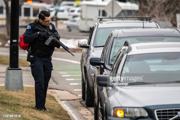 Police officer checks cars in the area after a gunman opened fire at a King Sooper's grocery store on March 22, 2021 in Boulder, Colorado. Ten...