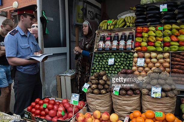 CONTENT] A police officer checks documents of seller from Central Asia during an action Russian cleanup against illegal trading at the Sennoy market...