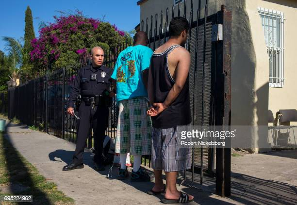 A police officer checks identities of possible street gang members May 21 2017 after the group was stopped for drinking in public a municipal offense...