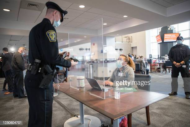 Police officer checks in to receive his COVID-19 vaccination at Gillette Staium's vaccination site on January 15, 2021 in Foxborough, Massachusetts....