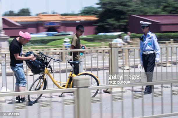 A police officer checks the identity of people in Tiananmen Square on the anniversary of the 1989 crackdown on democracy protestors in Beijing on...
