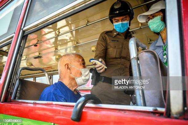 A police officer checks the temperature of an passenger at one of the checkpoints set up to stop the spread of the COVID19 novel coronavirus in...