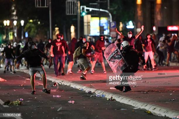 Police officer clashes with protesters near the National Assembly building in Belgrade, on July 10 during a demonstration against a weekend curfew...