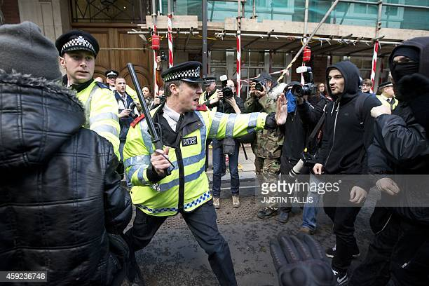 A police officer clashes with protesters outside the Conservative Campaign Headquarters after a march against student university fees in central...
