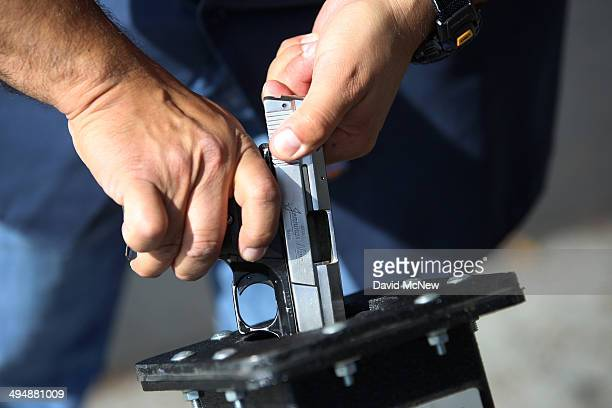 A police officer clears a surrendered Jennings Nine 9mm handgun at a gun buyback event that was announced by Los Angeles Mayor Eric Garcetti in the...