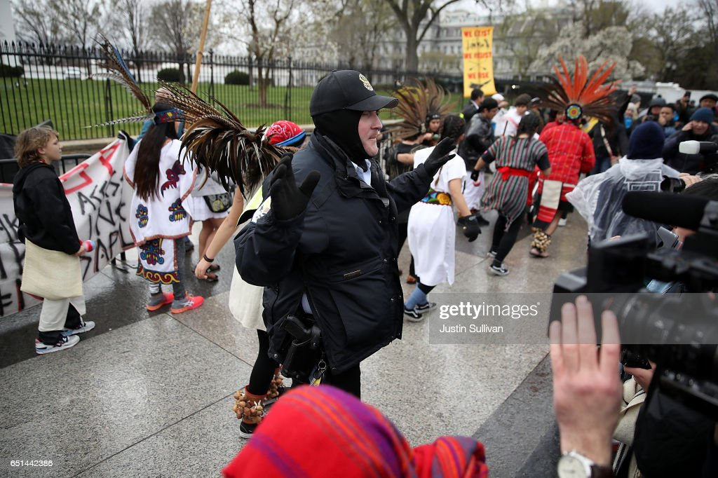 A police officer clears protesters off the sidewalk in front of the White House during a demonstration against the Dakota Access Pipeline on March 10, 2017 in Washington, DC. Thousands of protesters and members of Native nations marched in Washington DC to oppose the construction of the proposed 1,172 Dakota Access Pipeline that runs within a half-mile of the Standing Rock Sioux reservation in North Dakota.