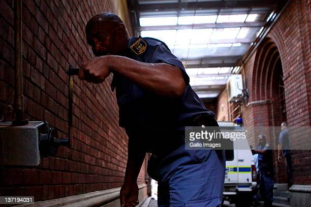 A police officer closes the gate to the Cape Town magistrates court to shield Dobrosav Gavric a Serbian fugitive seeking refugee status in South...