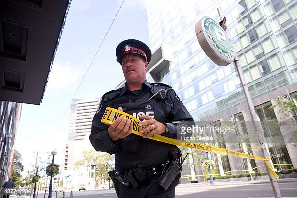 A police officer closes the sidewalk on Bay Street after shattered plane of glass rained down on Bay Street and Yorkville Avenue Thursday afternoon...