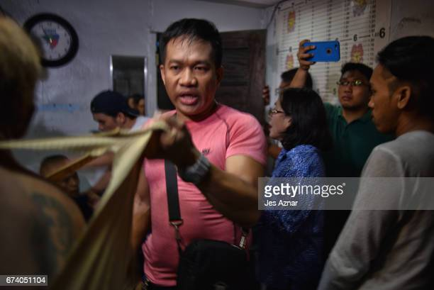 A police officer collars a detainee suspected of drug use detained at a small secret cell behind a wooden cabinet on April 27 2017 in Manila...