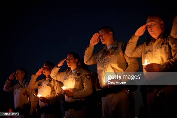 Police officer colleagues of Las Vegas Metropolitan Police Department Officer Charleston Hartfield salute while 'Taps' is played during a vigil for...