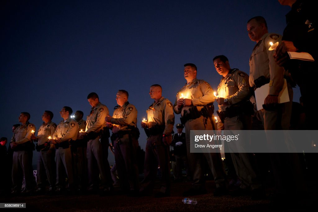 Police officer colleagues of Las Vegas Metropolitan Police Department Officer Charleston Hartfield hold candles during a vigil for Hartfield at Police Memorial Park on October 5, 2017 in Las Vegas, Nevada. Hartfield, who was off duty at the Route 91 Harvest country music festival on October 1, was killed when Stephen Paddock opened fire on the crowd killing at least 58 people and injuring more than 450. The massacre is one of the deadliest mass shooting events in U.S. history.