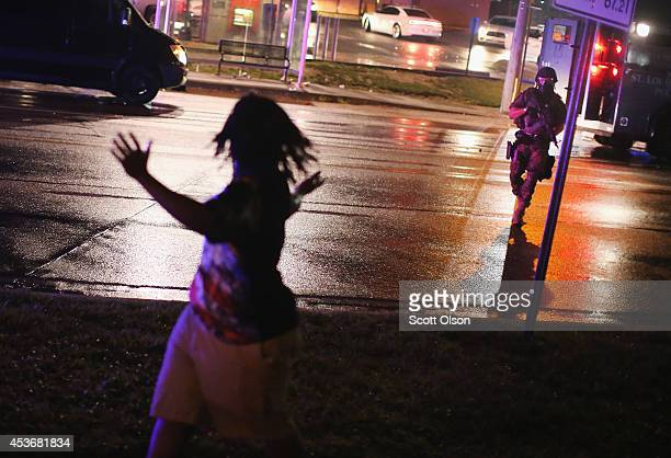 Police officer confronts a demonstrators during a protest over the shooting death of Michael Williams on August 15 2014 in Ferguson Missouri Police...