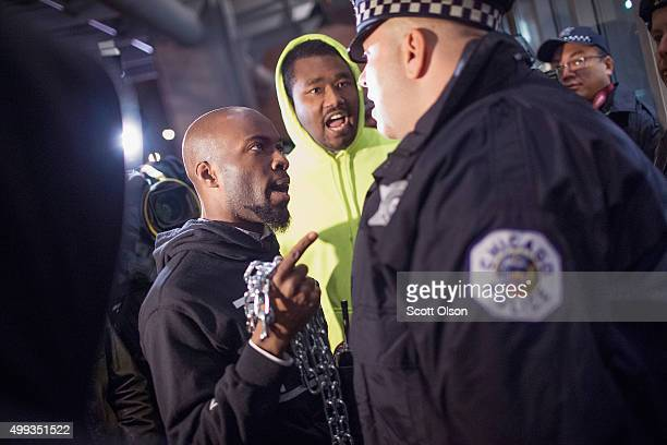 Police officer confronts a protester who tried to symbolically chain the doors to Chicago police headquarters during a prayer vigil and demonstration...