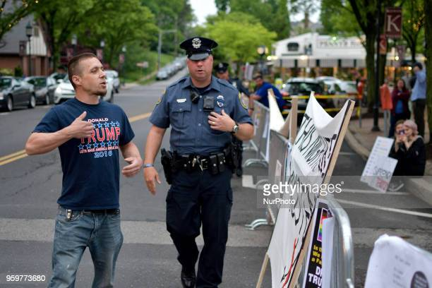 Police officer confronts a Trump supporter who faces of with a group of protestors across the street ahead of a tour stop by Tomi Lahren conservative...