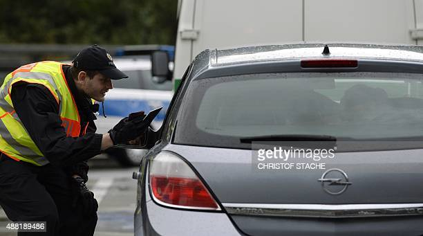 A police officer controls a car at a parking spot at the GermanAustria border near the village of Passau southern Germany on September 14 2015...