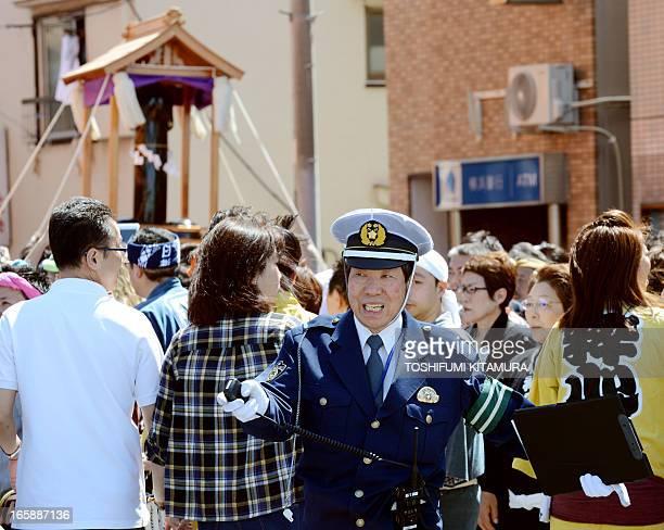 A police officer controls the crowds beside a phallusshaped portable shrine during the Kanamara festival near the Kanayama shrine in Kawasaki...