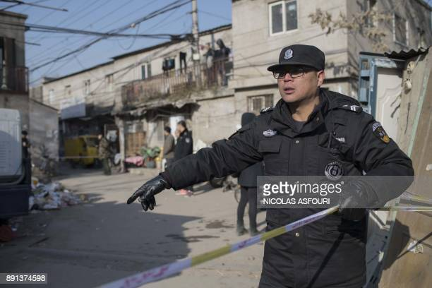 A police officer cordon off the site of a fire in a low income neighbourhood in Beijing on December 13 2017 A building fire killed five people and...