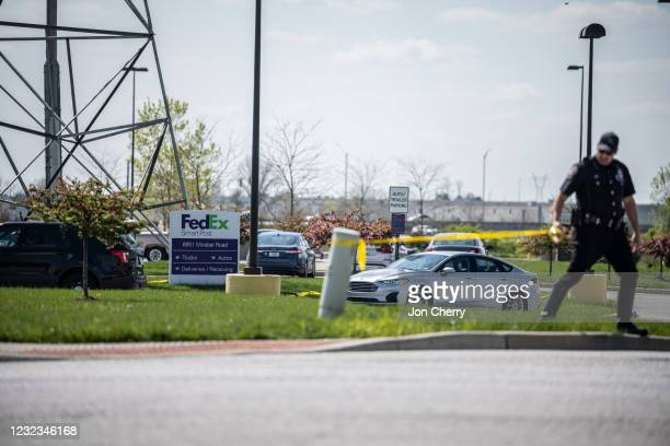 Police officer cordons off a road leading to the FedEx parking lot with caution tape on April 16, 2021 in Indianapolis, Indiana. The area is the...