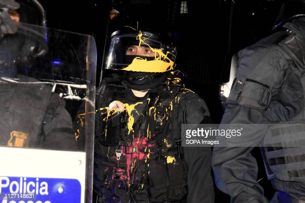 A police officer covered with paint seen looking on as he stands alert during the protest Hundreds of people demonstrate against the presence of the...