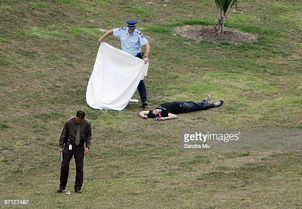 Police officer covers up the body of a young man, believed to be 19 years old, found in Basque Park, Newton on March 19, 2006 in Auckland, New...