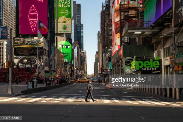 A police officer crosses the street in a nearly empty Times Square on March 12 2020 in New York United States Many New Yorkers are heeding the advice...