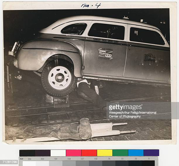 A police officer crouches under the rear end of taxi jacked up on a crate and garbage can as the dead body of a man who was hit by the cab lies...