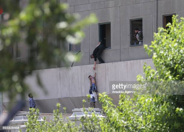 A police officer dangles a child from the window as the police conduct an operation against the attacker in the parliament building after gunmen...