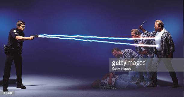 A police officer demonstrates the Air Taser stun gun which has a range of 15 feet and delivers a paralyzing electric shock to its target in this...