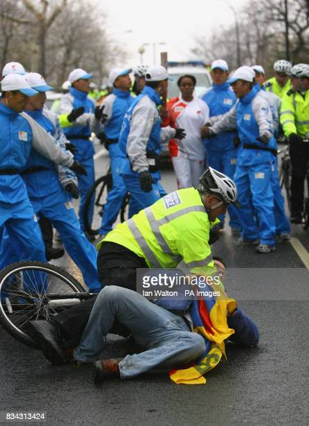 A police officer detains a proTibet demonstrator along the route of the relay of the Olympic torch during its journey across London on its way to the...