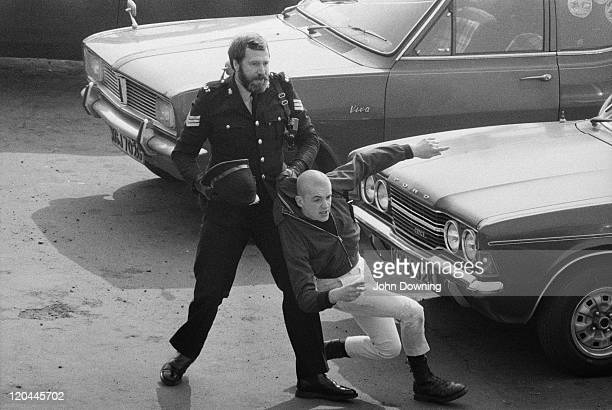 A police officer detains a skinhead in SouthendonSea Essex 7th April 1980