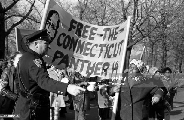A police officer directs protesters several of whom carry a 'Free the Connecticut Panther 14' banner with as they march during the 'Free Bobby Free...