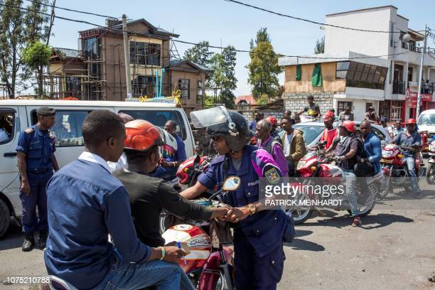 Police officer directs traffic near the university in Goma, on December 27 following a demonstration against the postponement, announced the day...
