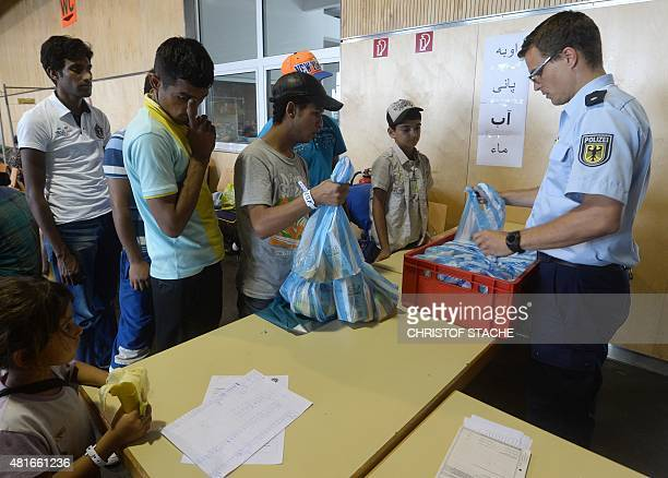 A police officer distributes food to refugees at the first registration point of the German federation police in Passau southern Germany on July 23...
