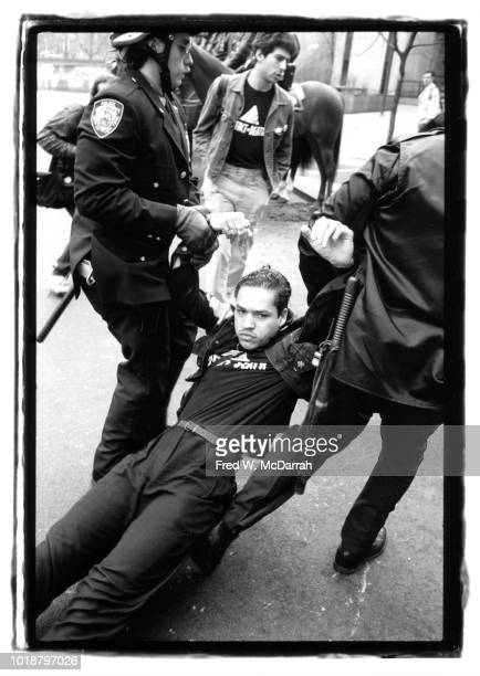 Police officer drag an unidentified protestor from ACT UP by his arms as they arrest him during an AIDS demonstration in City Hall Park New York New...