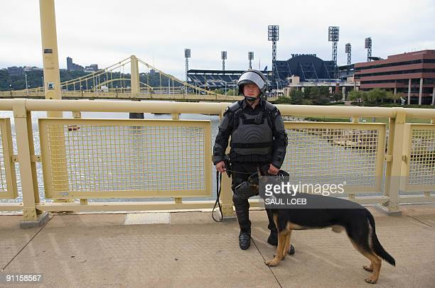 A police officer dressed in riot gear along with his guard dog watch as thousands of demonstrators march through downtown Pittsburgh Pennsylvania on...